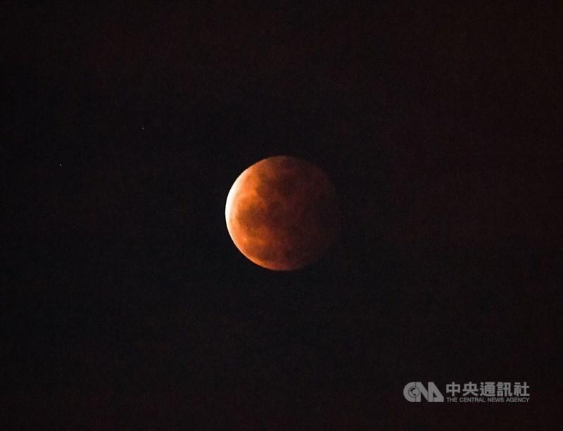 天文景觀月全食26日晚間登場,適逢年度最大滿月,夜空中可見暗紅色月面,台北民眾抬頭就可在夜空中欣賞月食過程。中央社記者鄭清元攝 110年5月26日