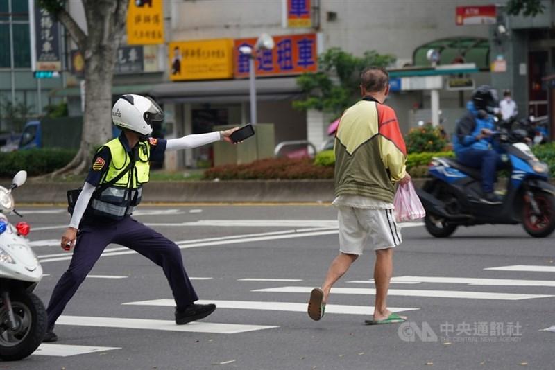 指揮中心副指揮官陳宗彥26日表示,全台有5萬名警消列在前3優先疫苗施打順位。圖為一名員警20日在北市街頭巡邏時,看見沒戴口罩的民眾,進行攔檢勸導。(中央社檔案照片)