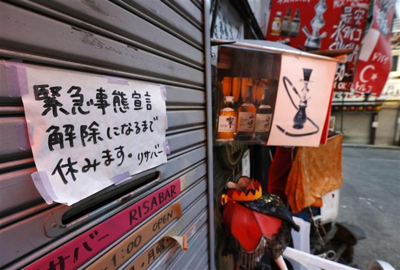 日本10都道府縣因疫情實施「緊急事態宣言」,日本政府28日召開專家會議,同意延長實施到6月20日。圖為東京新宿店家鐵門上貼著因緊急事態宣言而暫停營業的紙張。(共同社)