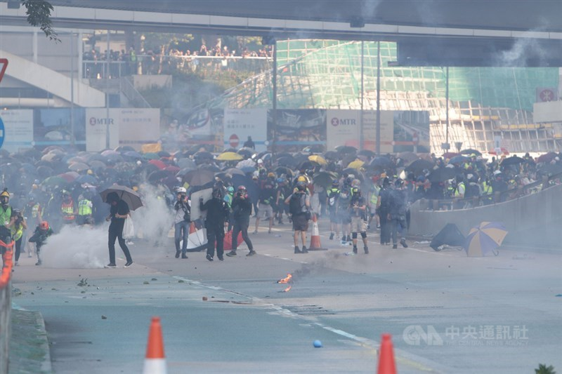 香港壹傳媒集團創辦人黎智英等10人承認2019年10月1日組織未經批准集結等罪,被法院判囚緩刑至18個月不等。圖為2019年10月1日香港市民發起「遍地開花」示威遊行,警方以催淚瓦斯驅離。(中央社檔案照片)
