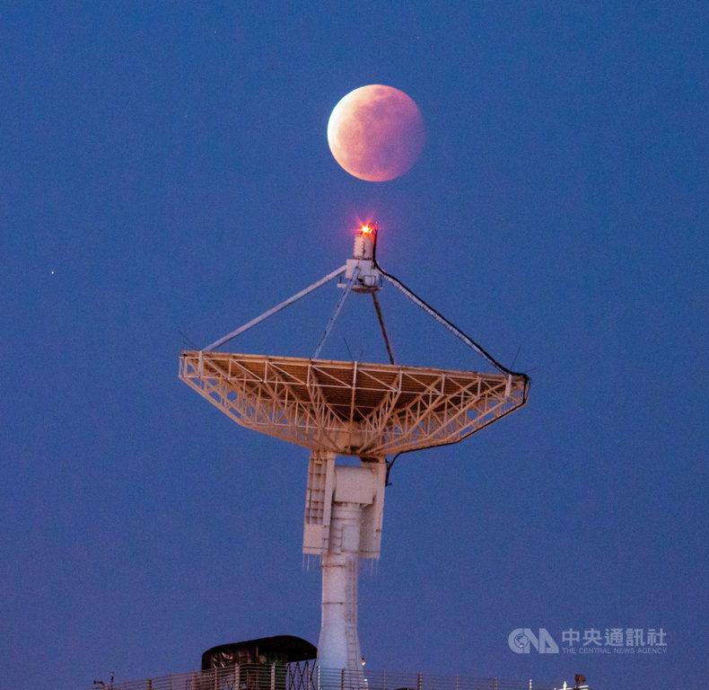 中央大學天文所碩士班研究生譚瀚傑事先估算,發現在月全食發生當下,站在中大太空及遙測研究中心西北方300公尺外的田間,就可同時捕捉「超級血月」和台灣最大的13米碟型大天線並陳奇景,成功拍下彌足珍貴的畫面。(譚瀚傑提供)中央社記者陳至中台北傳真  110年5月28日
