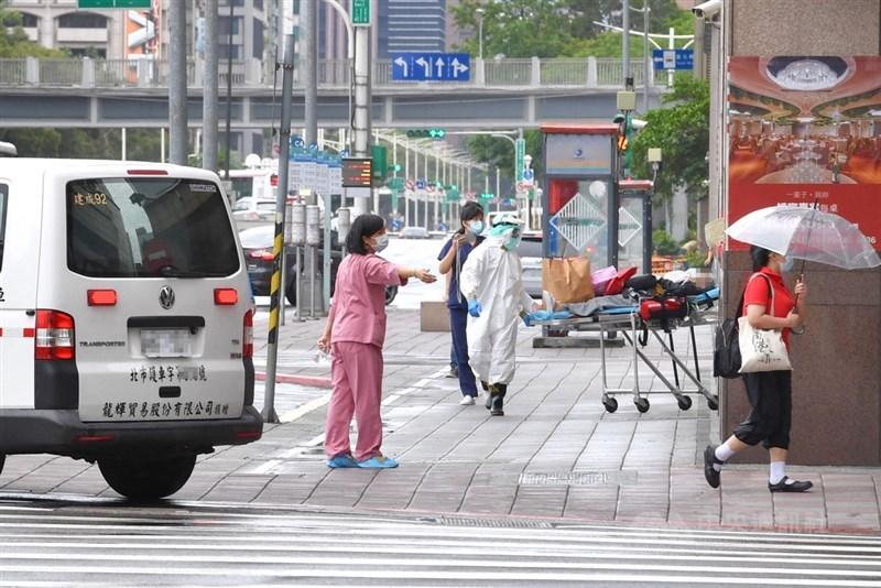 染疫者在家中、集中檢疫所猝死狀況頻傳,疫情指揮中心擬訂新版分流規定,未來只有60歲以下、無慢性病的患者才能居家隔離。圖為台北市一處防疫旅館,病患在醫護人員安全護送下,自防疫旅館內移出,由救護車送往醫院。中央社記者王飛華攝 110年5月29日