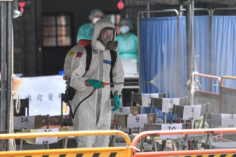 COVID-19疫情蔓延全球,台灣累計78死超越SARS。圖為國軍化學兵在萬華剝皮寮快篩站全面消毒。(中央社檔案照片)