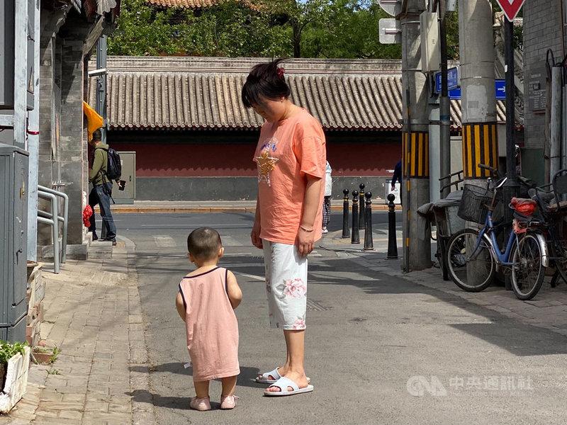中共中央政治局會議5月31日提出實施三孩生育政策,但中國網友普遍認為「生得起、養不起」,對生育三孩持保留態度。圖為北京街頭帶著幼童的家長。中央社記者繆宗翰北京攝 110年6月1日