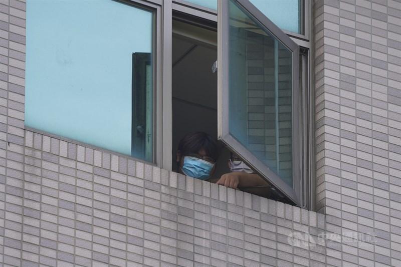 中國文化大學校內大倫館有4名學生確診武漢肺炎,校方2日安排大倫館住宿生進行快篩。有住宿生從窗口好奇探看媒體在封鎖線外採訪。中央社記者徐肇昌攝 110年6月2日
