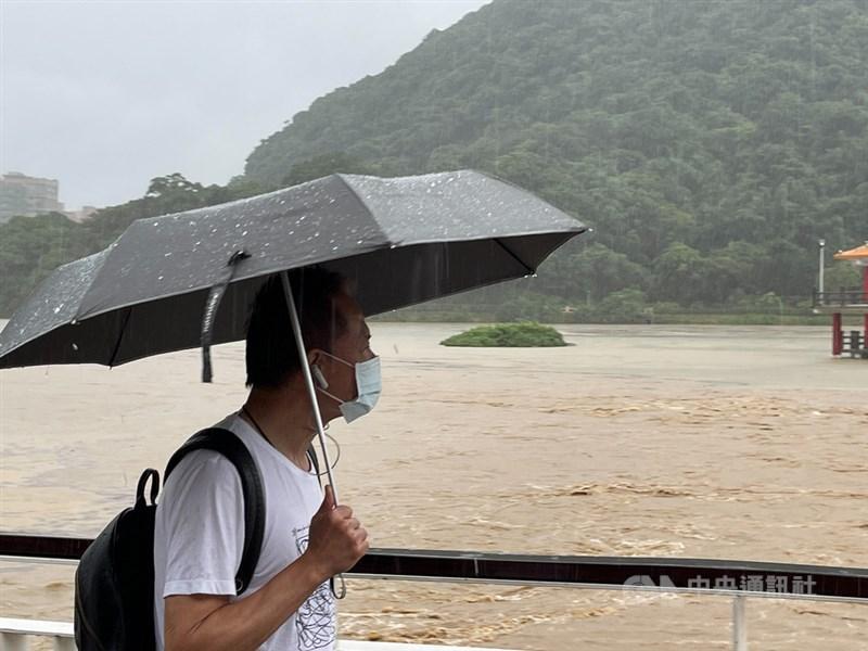 氣象局預報梅雨鋒面5日至7日將在台灣上空徘徊,週休假日降雨更明顯,西半部及東北部防大雨或豪雨。圖為4日午後大湖公園因豪雨成一片汪洋,民眾撐著傘快步通行。中央社記者王飛華攝 110年6月4日