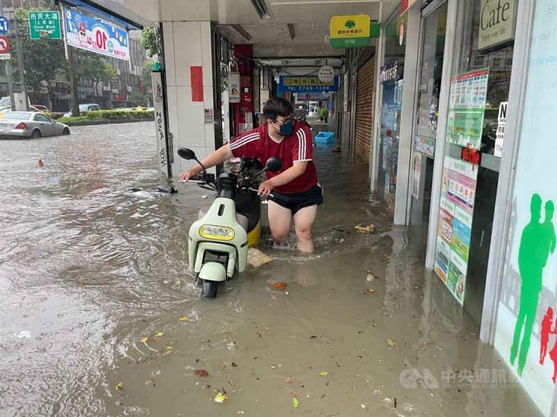 受梅雨鋒面及颱風彩雲外圍環流影響,水利署4日針對台北市文山區、信義區發布淹水一級警戒。圖為信義區永吉路淹水情形,民眾涉水牽機車。中央社記者張新偉攝 110年6月4日