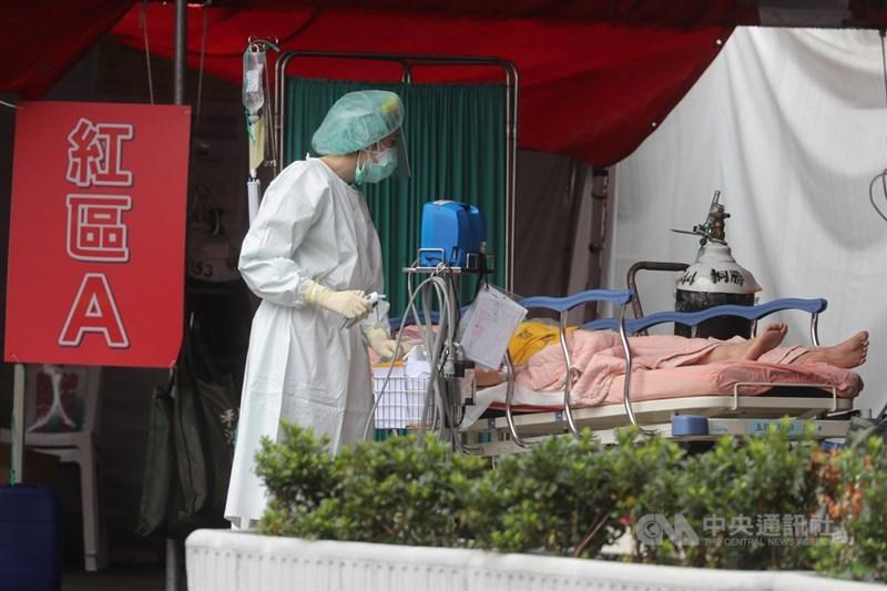 台北市確診個案43%為家戶感染,疫情指揮中心指揮官陳時中4日分析可能有潛伏期較久、發病後送安置較慢等3大原因。圖為北市聯合醫院忠孝院區醫護在戶外照護病患。(中央社檔案照片)