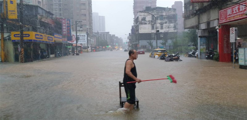 受梅雨鋒面及颱風彩雲外圍環流影響,水利署針對台北市文山區、信義區發布淹水一級警戒。圖為民眾在泥濘水中行走,拿掃把準備清理環境。(台北市政府提供)中央社記者陳怡璇傳真 110年6月4日