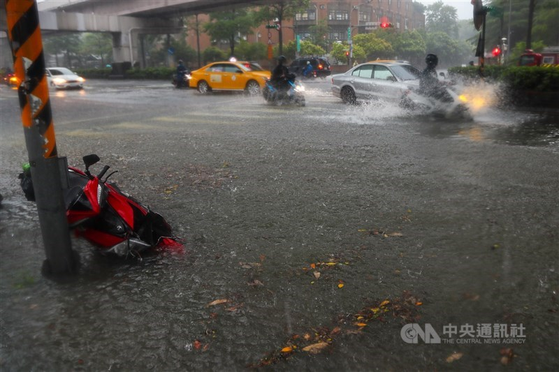 受颱風來襲影響,4日北市午後降下大雨,基隆路3段出現淹水的情況,機車騎士在雨中奔馳,激起水花。中央社記者王騰毅攝 110年6月4日