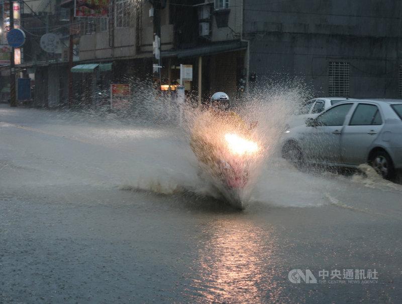 高雄市豪雨不斷,岡山區嘉興路一帶6日清晨積淹水約半個輪胎深,早上外出的人車不清楚路況,涉水通行,路面濺起一尺高的水花。中央社記者王淑芬攝 110年6月6日