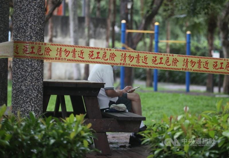 COVID-19疫情蔓延全球,台灣5日新增476例本土病例、35例校正回歸,雙北占最大宗。圖為北市公園大多數設施已拉起封鎖線暫停使用,民眾戴著口罩在公園座位區休息滑手機。中央社記者張新偉攝 110年6月5日