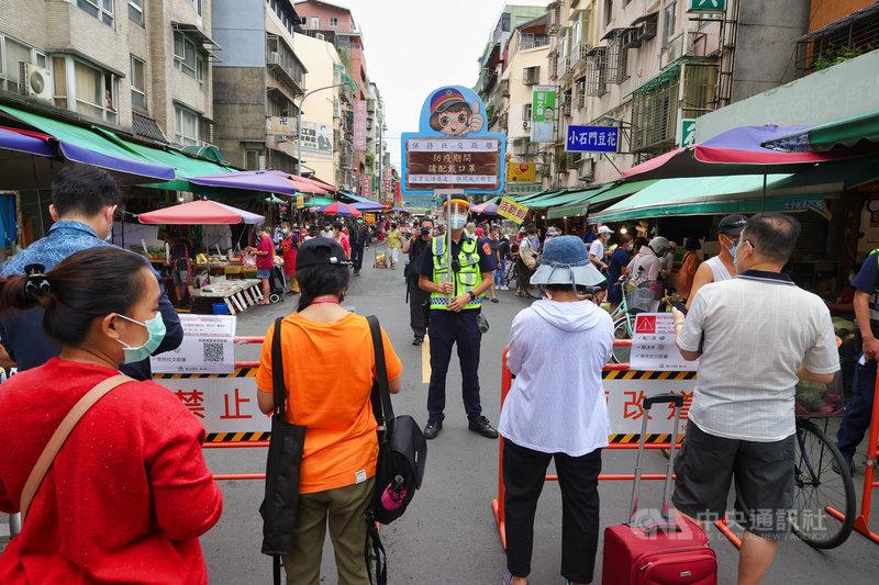國內COVID-19疫情嚴峻,政府呼籲民眾減少採買次數避免群聚,台北市警方6日在傳統市場入口處管制並進行相關宣導。中央社記者謝佳璋攝 110年6月6日