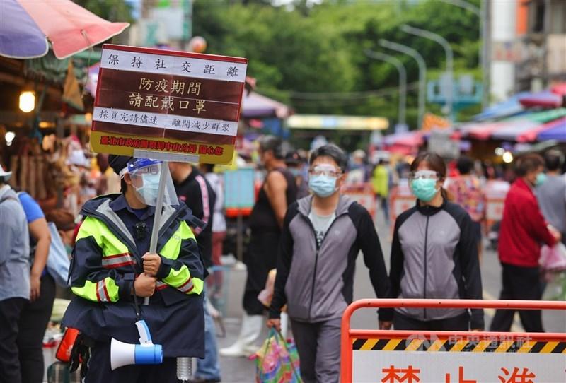 國內COVID-19疫情嚴峻,台北市警方6日在傳統市場舉牌宣導,提醒民眾戴口罩、保持社交距離,採購完畢儘速離開。中央社記者謝佳璋攝 110年6月6日