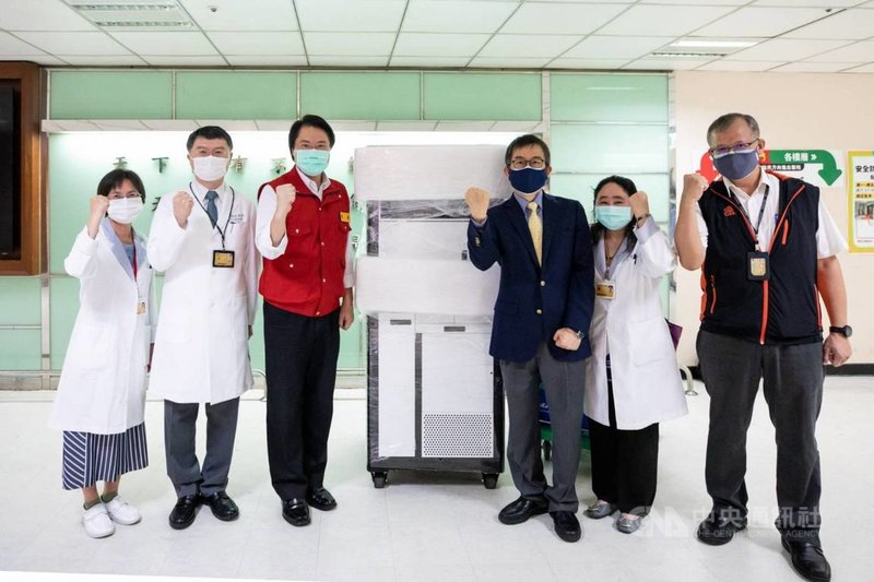基隆長庚醫院引進「全自動新冠病毒檢測機台」,PCR核酸檢測量能從原本每天140例,可以再增加700例,總數可達每天840例以上。機台運至基隆時,市長林右昌(左3)特地前往視察,並為醫檢人員加油打氣。(基隆市政府提供)中央社記者王朝鈺傳真  110年6月8日
