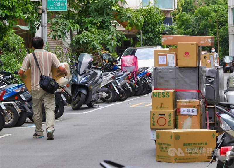 國內COVID-19疫情嚴峻,民眾減少出門在家網購,導致包裹數量大增,宅配通、黑貓宅急便與嘉里大榮等物流業者調整低溫寄送服務。圖為物流人員8日在街頭理貨、送貨。(中央社檔案照片)