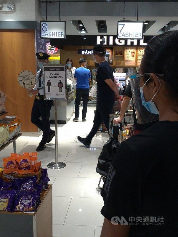 菲律賓內政部發言人馬拉亞表示,5月31日到6月6日,菲律賓發生6萬4000多起違反抗疫隔離措施的案例。圖為大馬尼拉地區超市警衛3月21日舉牌,請民眾保持社交距離。中央社記者陳妍君馬尼拉攝 110年6月10日