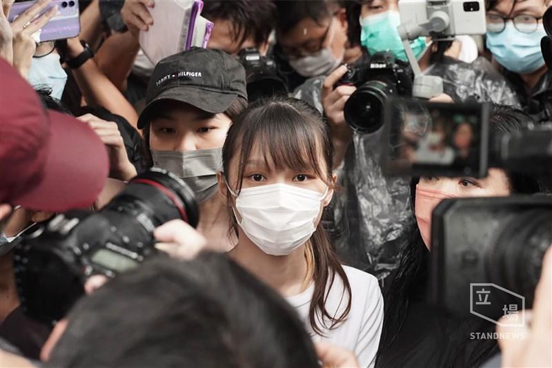 前香港眾志副秘書長周庭(前中)12日刑滿出獄,現場聚集大批媒體,有人大喊「周庭加油」,她未發一語,登上小客車離開。(圖取自立場新聞)