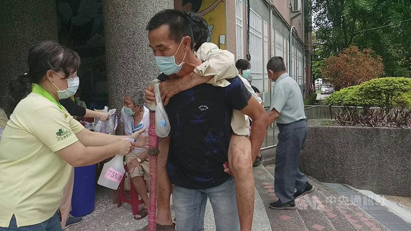 嘉義縣85歲以上長輩15日開始施打武漢肺炎(COVID-19 ,2019冠狀病毒疾病)疫苗,水上鄉1名中年男子揹著行動不便的母親排隊打疫苗,舉止感動醫護人員。(台中榮總灣橋分院提供)中央社記者蔡智明傳真 110年6月15日