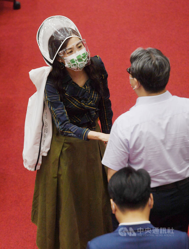 民進黨立委林宜瑾(左)16日出席立法院會,戴口罩、透明面罩、再加上防護連帽外套,她表示,這些裝備可以保護她搭高鐵南北奔波。中央社記者施宗暉攝  110年6月16日