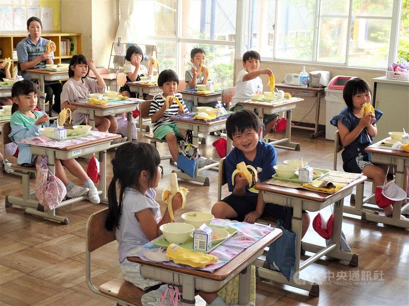 駐日代表謝長廷18日中午造訪東京奧運台灣隊接待城茨城縣笠間市,贈香蕉給當地學童,學童們吃得津津有味。中央社記者楊明珠茨城攝 110年6月18日