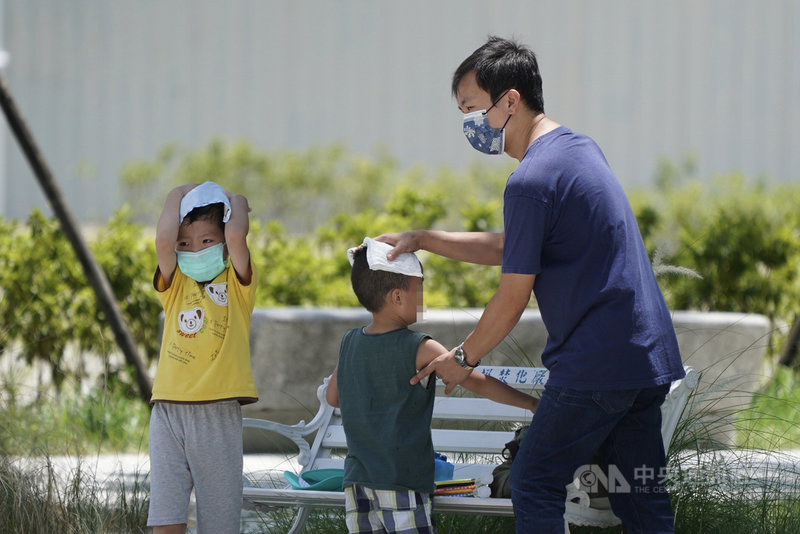 西南風沉降影響,中央氣象局18日上午發布10縣市高溫燈號,台北市、新北市、台東縣地區為橙色燈號,有連續出現攝氏36度高溫的機率。家長帶孩子出外運動後,幫他們擦汗。中央社記者徐肇昌攝  110年6月18日
