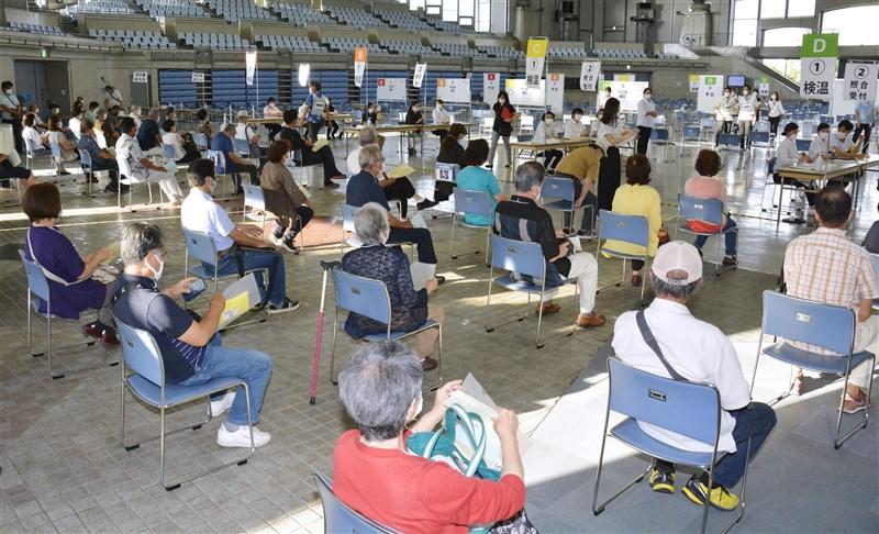 日本東京都等地「緊急事態宣言」20日結束,沖繩縣因為疫情暫未趨緩,成日本唯一實施緊急事態宣言的地區。圖為沖繩疫苗施打中心等待接種的老年人。(共同社)