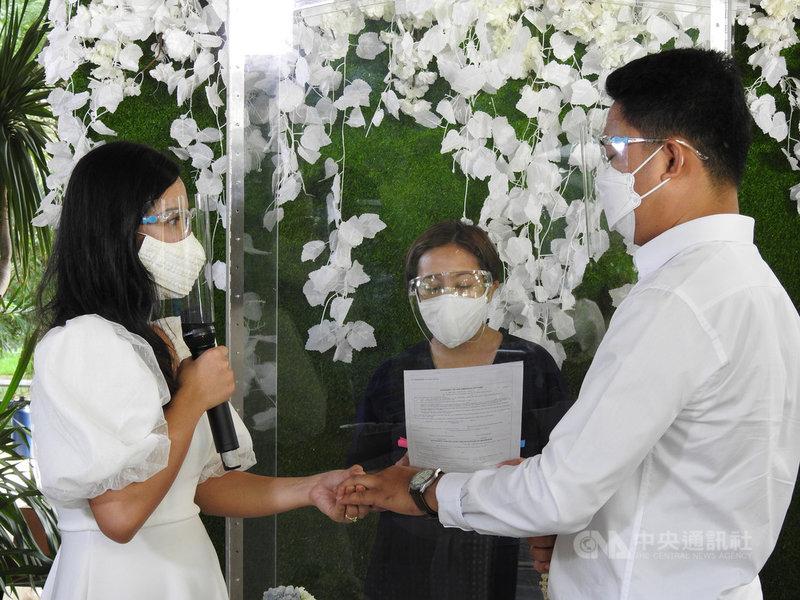 2019冠狀病毒疾病疫情下,大馬尼拉地區馬卡蒂市聯合婚禮移師公園。圖為新人隨著市長畢乃宣讀婚禮誓詞,並互戴婚戒,攝於6月10日。中央社記者陳妍君馬尼拉攝 110年6月23日