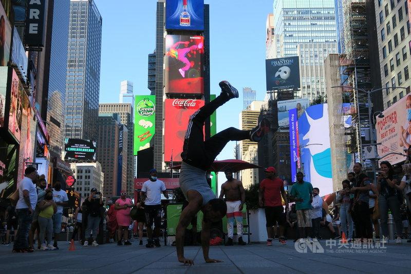 紐約2019冠狀病毒疾病疫情趨緩,熱門景點時報廣場人氣回籠,街頭藝人在民眾圍觀下熱舞。圖攝於6月10日。中央社記者尹俊傑紐約攝 110年6月23日