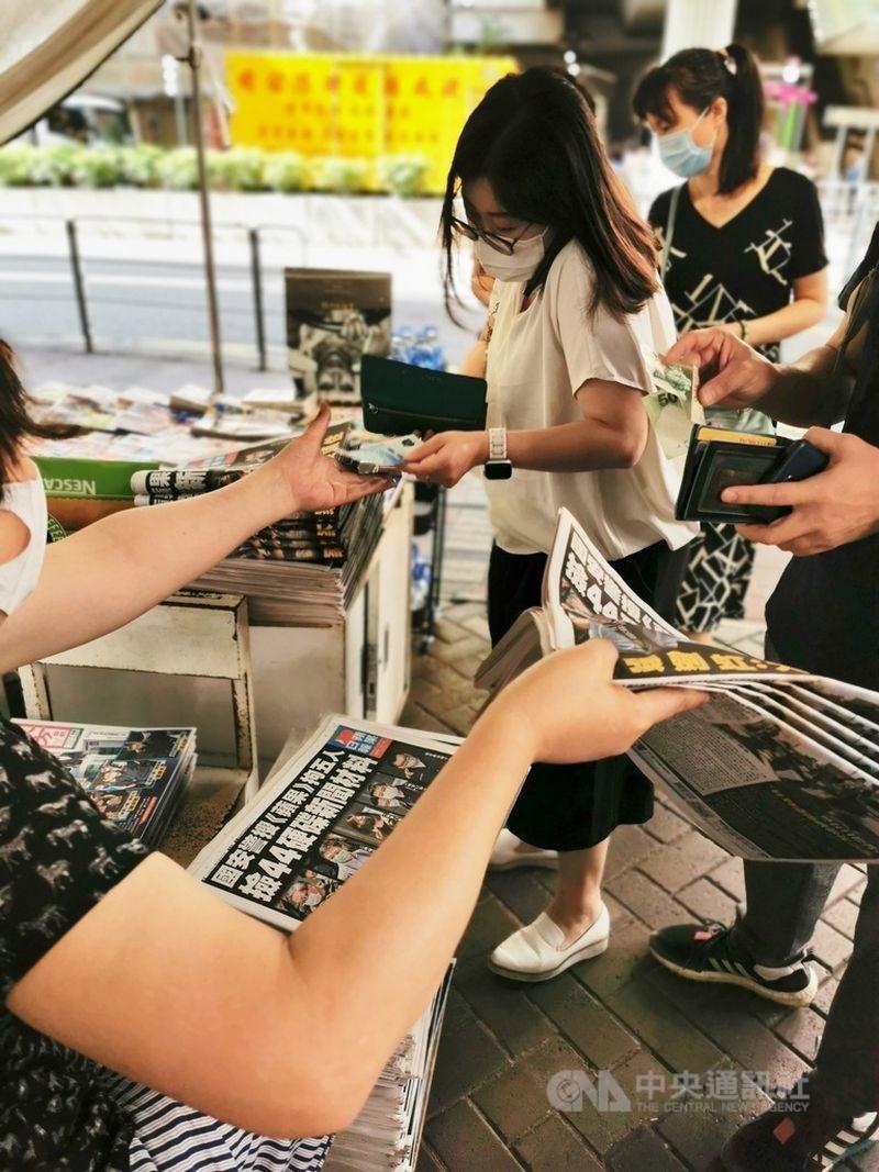 據了解,香港蘋果日報將於24日停止營運。圖為香港蘋果5位高層被拘捕後加印50萬份報紙,大批市民一早購買以示支持。(中央社檔案照片)
