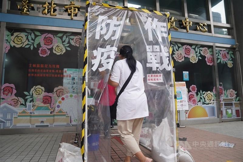 台北市士林區行政中心外設置隧道式噴霧消毒,進入洽公的民眾必須徹底消毒,通道口貼著「防疫作戰」提醒民眾防疫不鬆懈。中央社記者徐肇昌攝 110年6月23日