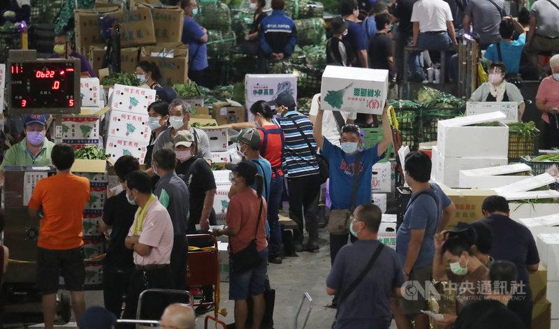 位於台北市萬大路的第一果菜批發市場,24日零時起,陸續有貨車抵達市場送、卸貨。市場內的承銷商、貨運司機等出示快篩陰性文件才進場,凌晨3點左右,工作人員開始展開喊價、販售。中央社記者張新偉攝 110年6月24日