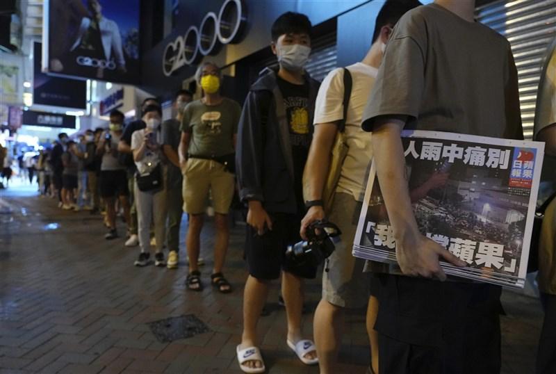 營運26年的香港蘋果日報24日出版最後一份報紙,頭報以「港人雨中痛別,『我哋(們)撐蘋果』」為題,大批民眾在街頭排隊購買。(美聯社)