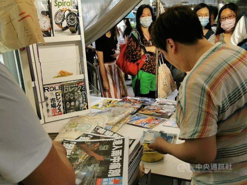 中國實施「港區國安法」後,民主派報紙香港蘋果日報被迫停刊。美國總統拜登24日呼籲北京停止打壓媒體。圖為香港蘋果日報24日出版最後一份報紙,大批讀者在報攤排隊購買表達支持。(中央社檔案照片)