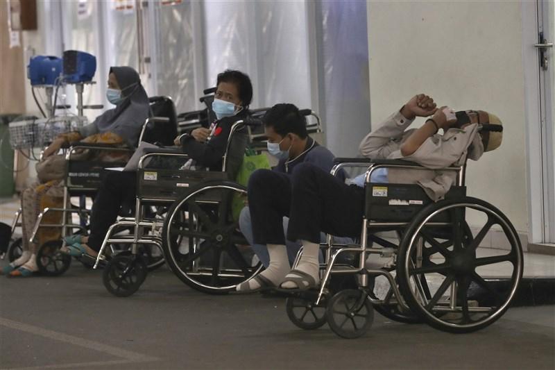 印尼27日新增逾2萬1000起COVID-19病例,改寫單日最高紀錄。圖為病人24日在雅加達一間醫院急診室外等待就醫。(美聯社)