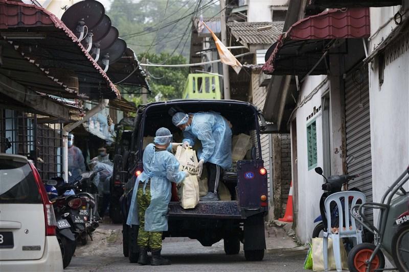 馬來西亞實施全面封鎖措施一個多月,疫情仍居高不下,9日新增9180人確診創新高。圖為馬來西亞人員分送物資。(美聯社)
