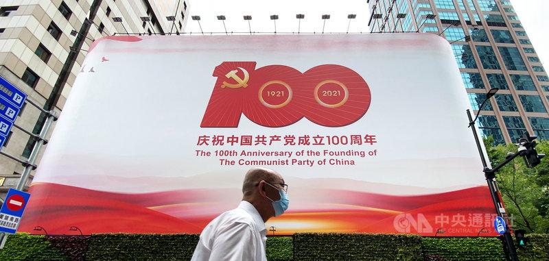 中共百年黨慶將於7月1日到來。圖為一名民眾途經上海黃浦區慶祝黨慶的巨型看板。中央社記者沈朋達上海攝 110年6月29日