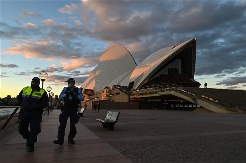 Delta變異株擴散,澳洲雪梨、達爾文、伯斯、布里斯本相繼採取防疫居家令,如今有約1000萬人受到封城影響。圖為26日警察在雪梨歌劇院外巡邏。(安納杜魯新聞社)