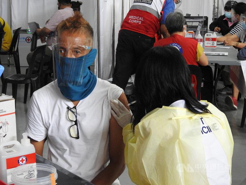 菲律賓政府跨部門抗疫工作小組決議,自低風險地區接種兩劑COVID-19疫苗的旅客,抵菲後僅需隔離7天,低風險地區包括台灣。圖為菲律賓紅十字會人員30日為民眾接種疫苗。中央社記者陳妍君馬尼拉攝 110年6月30日