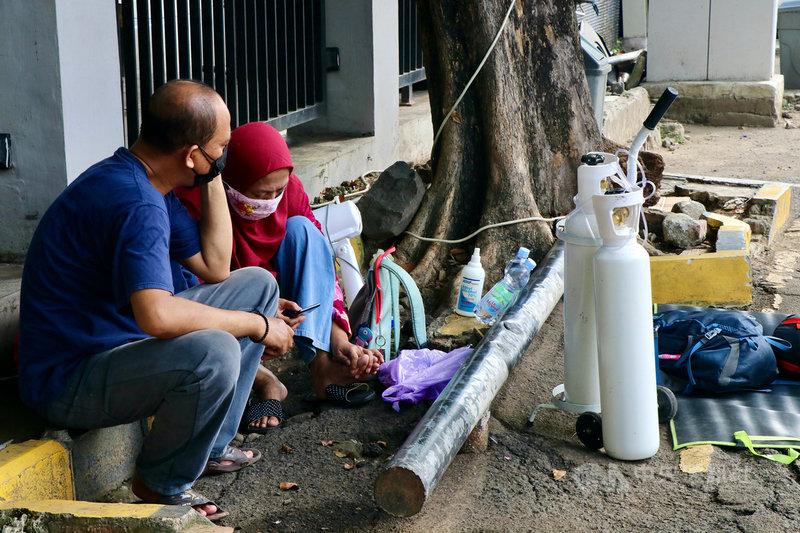 印尼單日新增確診連日破2萬例,疫情嚴峻,有就醫的民眾自備氧氣筒等待病床。圖攝於6月30日。中央社記者石秀娟勿加西攝 110年7月1日