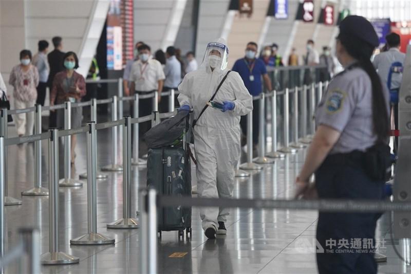 中央流行疫情指揮中心宣布,2日起所有入境者一律在機場進行核酸檢驗(PCR)採檢。圖為旅客穿著防護衣,推著行李依動線前往篩檢。中央社記者徐肇昌攝 110年7月2日