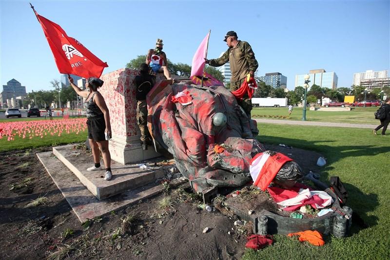 加拿大抗議人士1日高喊「種族滅絕不值得驕傲」口號,並將英國女王維多利亞雕像推倒洩憤。(路透社)