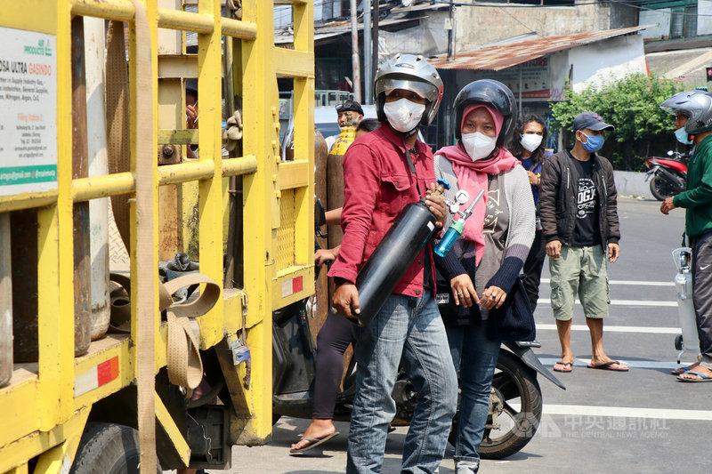 印尼疫情升溫,患者激增,雅加達南區一個醫療氧氣加氣站4日有許多民眾帶著空醫療氧氣瓶來補充氧氣。中央社記者石秀娟雅加達攝  110年7月4日