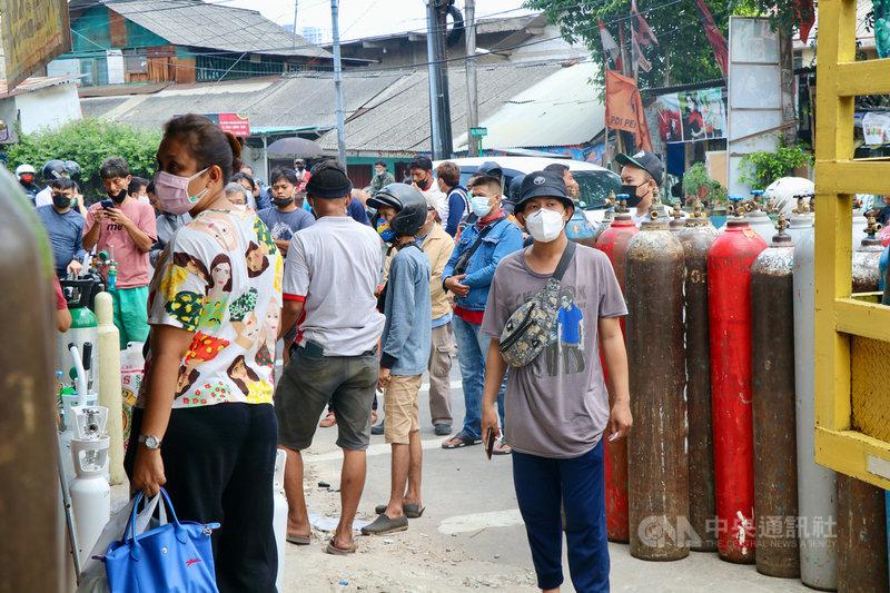 印尼5日新增將近3萬例確診,雅加達接連2天突破萬人確診,患者激增,多地爆出醫療氧氣不足的危機,當局表示,會以最大量生產醫療氧氣。圖為民眾4日在雅加達南區的一個氧氣補充站等待購買氧氣。中央社記者石秀娟雅加達攝  110年7月5日