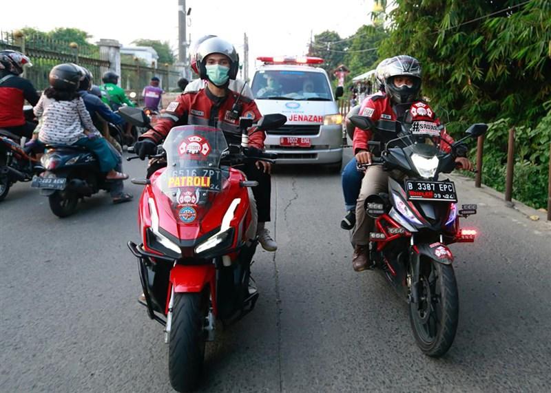 印尼一群志工無懼染疫風險,騎機車穿梭在擁擠的街頭替救護車開道,以讓患者盡早到院治療。(路透社)