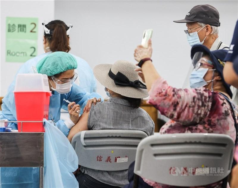 指揮中心8日開放全國第9、10類疫苗接種對象登記意願,截至9日下午2時已有超過200萬人登記。圖為9日上午民眾前往信義國中疫苗接種站施打疫苗,並拿起手機自拍留念。中央社記者鄭清元攝 110年7月9日