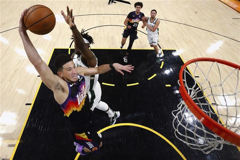 NBA鳳凰城太陽隊王牌射手布克(前)9日轟下全隊最高31分,搭配主控保羅23分進帳,終場118比108擊敗密爾瓦基公鹿隊,在總冠軍賽2比0領先。(美聯社)