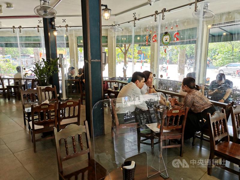 越南12日新增超過2000例COVID-19本土病例,一連5天寫下新紀錄。首都河內市過去一週共有超過60人染疫,決定自13日起再度暫停餐飲業內用服務只能做外帶生意。圖為12日下午在咖啡廳閒聊的越南民眾。中央社記者陳家倫河內攝 110年7月12日