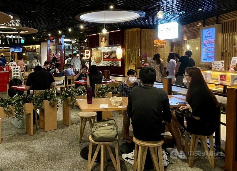 新加坡疫情保持穩定,12日起放寬餐廳內用人數至最多5人一桌,圖為實龍崗地鐵站附近一家商場餐廳的內用民眾。中央社記者侯姿瑩新加坡攝 110年7月12日