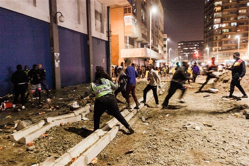 南非前總統朱瑪因藐視法庭罪7日入監服刑15個月,引發支持者大規模暴動,9日開始四處洗劫商家與縱火。圖為德班市11日晚間街頭一片混亂。(法新社)